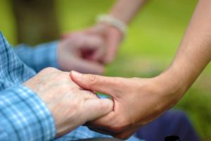 Home Care Assistant holding client's hand