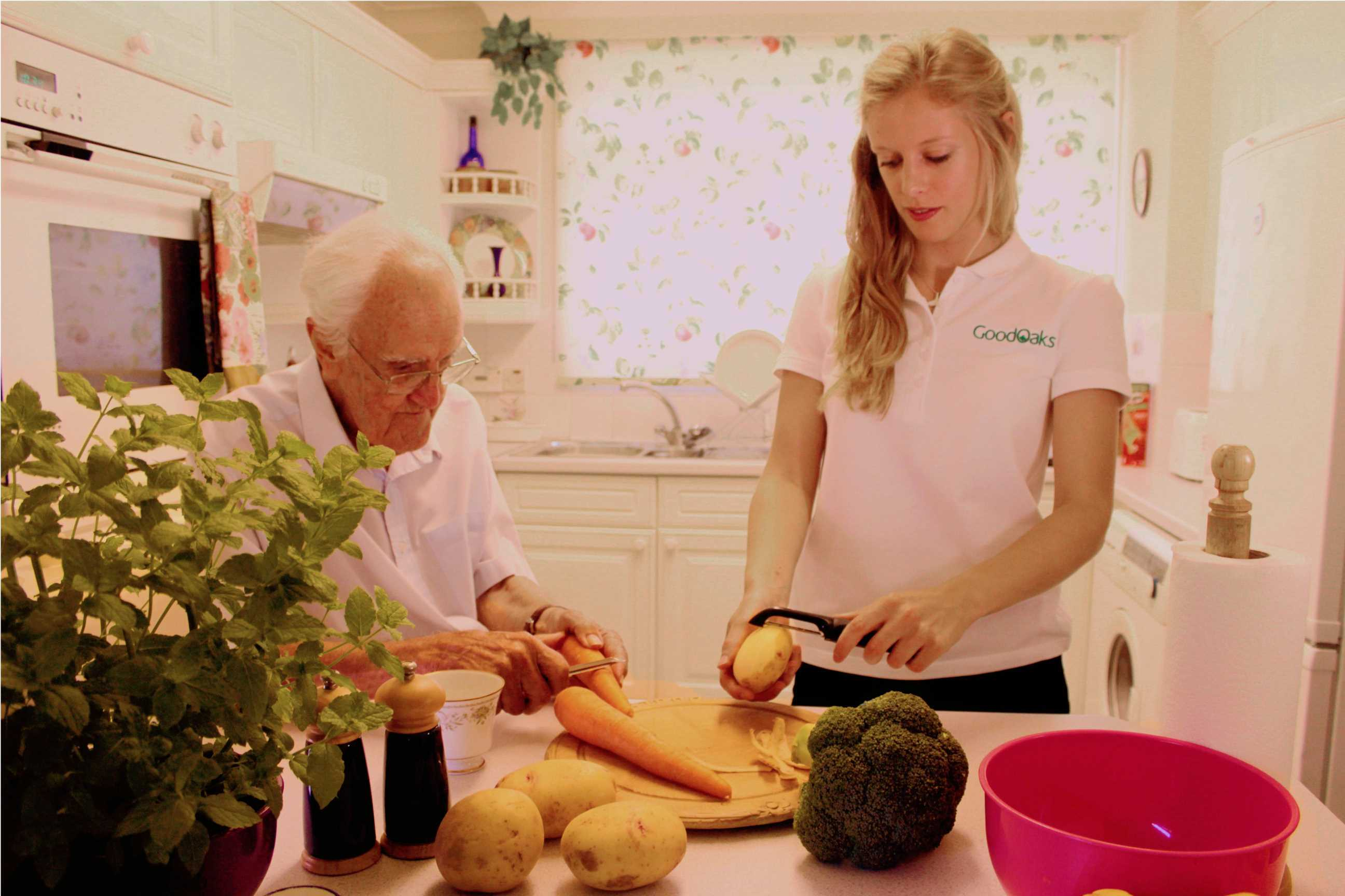 Home Carer Helps Elderly Client Prepare Vegetables