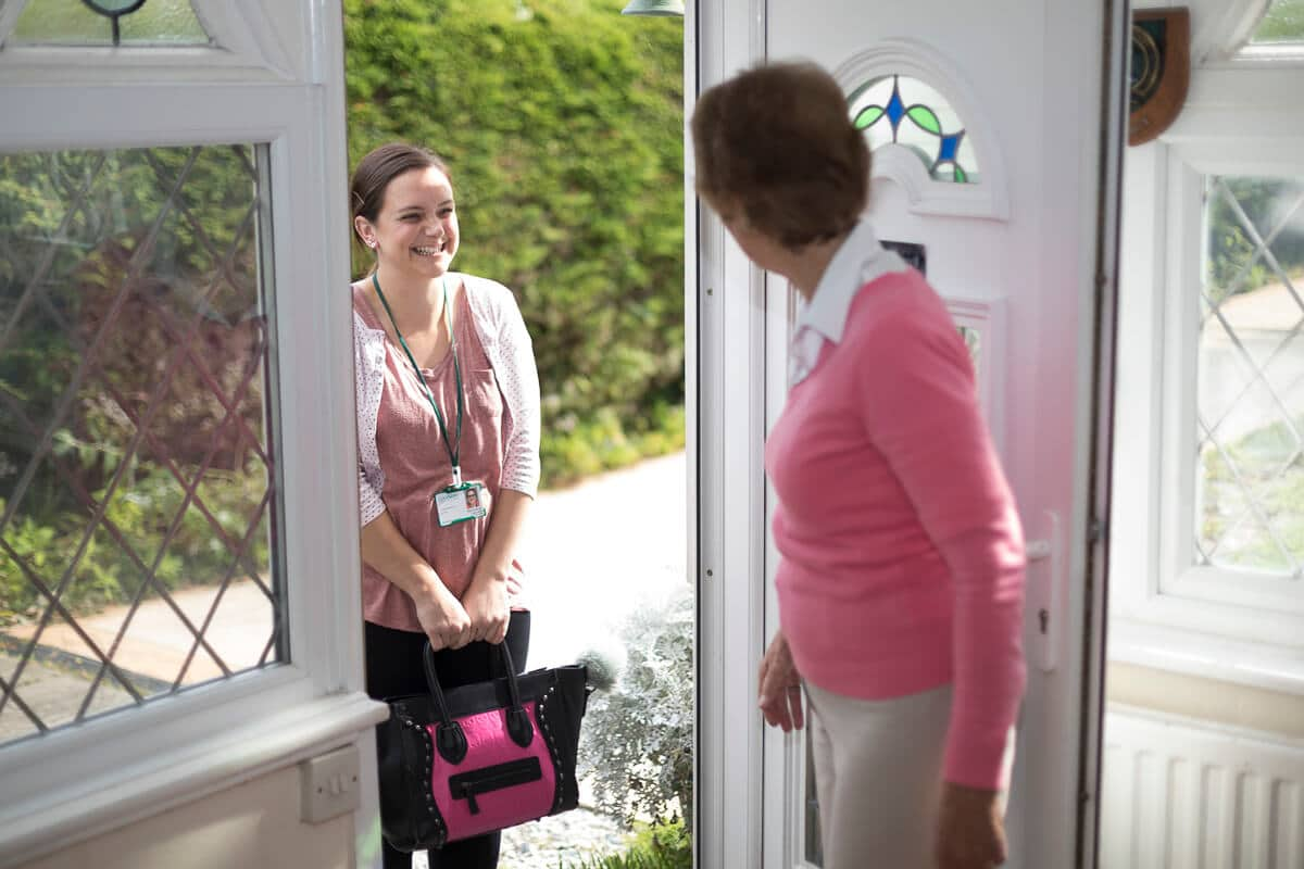 Elderly Lady Opening Front Door to Carer